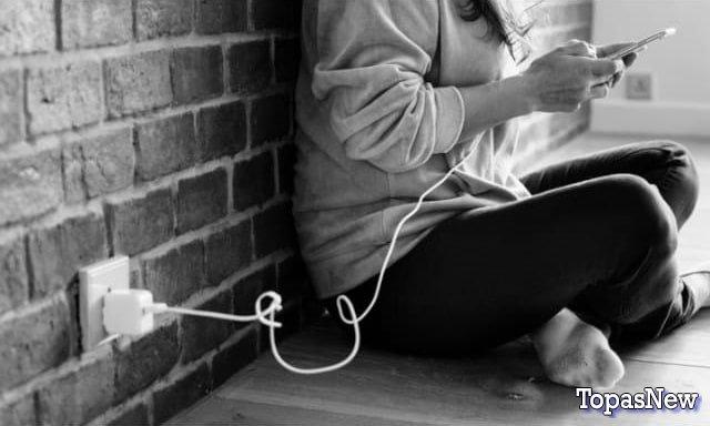 Человек сидит у стены заряжая телефон - картинка