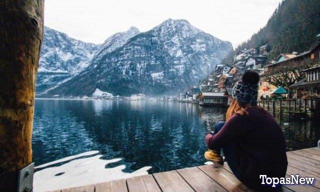 Девушка сидит и смотрит на горы и озеро - картинка